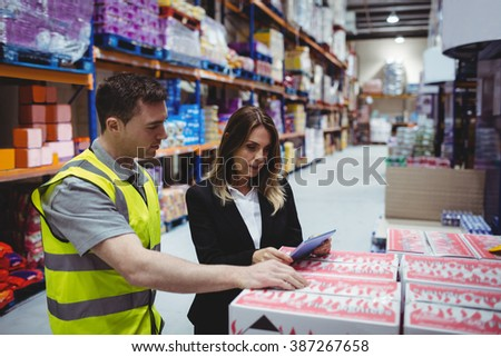 Warehouse manager and worker looking at tablet in warehouse - stock photo