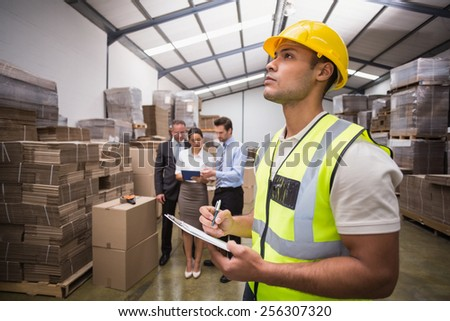 Warehouse manager checking his inventory in a large warehouse - stock photo
