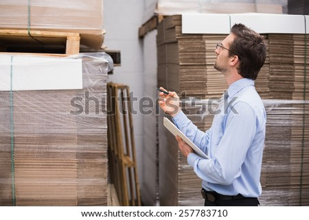 Warehouse manager checking his inventory in the warehouse - stock photo