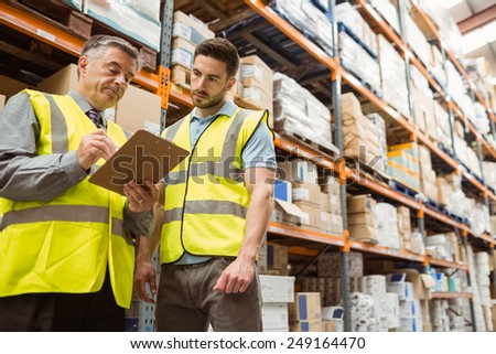 Warehouse manager speaking with foreman in a large warehouse - stock photo