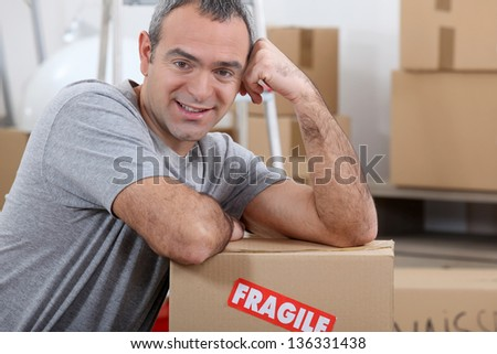 Warehouse manager stood by boxes - stock photo