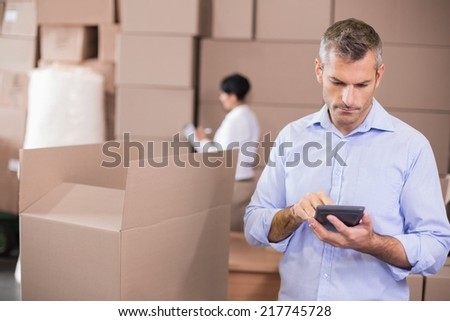 Warehouse manager using his calculator in a large warehouse - stock photo