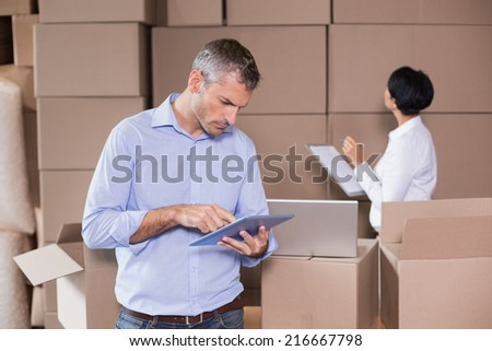 Warehouse manager using his tablet pc in a large warehouse