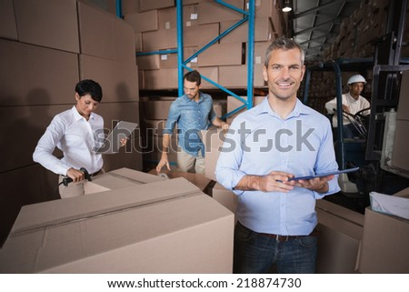 Warehouse manager using his tablet pc in a large warehouse - stock photo