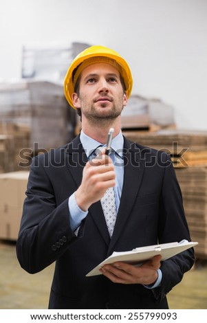 Warehouse manager wearing hard hat checking inventory in warehouse