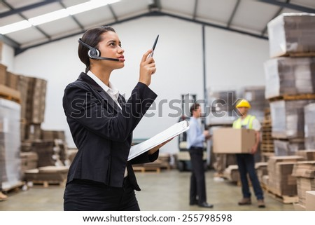 Warehouse manager wearing headset checking inventory in a large warehouse - stock photo