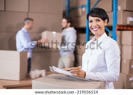 Warehouse manager writing on clipboard in a large warehouse - stock photo