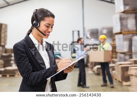 Warehouse manager writing on clipboard in warehouse - stock photo