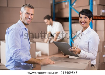 Warehouse manager writing on clipboard talking to colleague in a large warehouse - stock photo