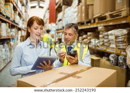 Warehouse managers looking at tablet pc in a large warehouse - stock photo