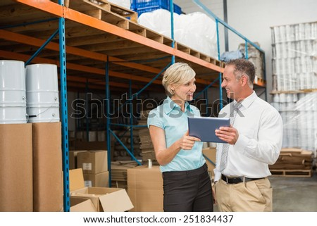 Warehouse managers using tablet pc in a large warehouse