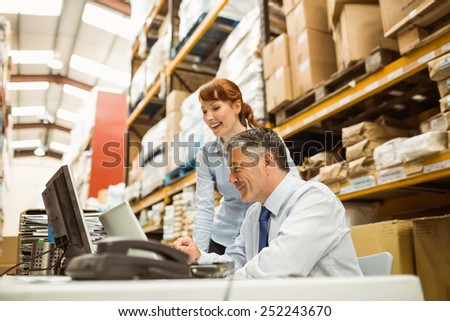 Warehouse managers working together on laptop in a large warehouse - stock photo