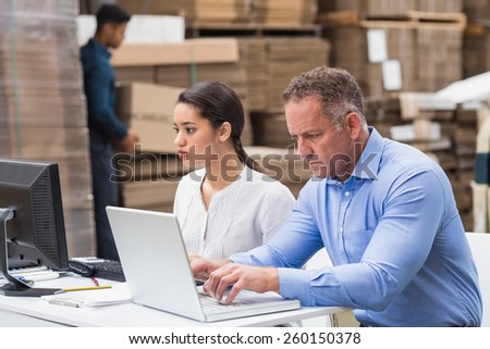 Warehouse managers working with laptop at desk in a large warehouse - stock photo