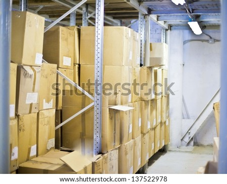 Warehouse shelf with cardboard boxes and goods  Interior of modern warehouse, many boxes - stock photo