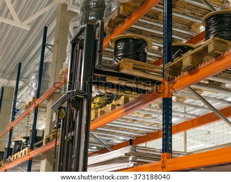 Warehouse storage racks with goods and forkslift. - stock photo