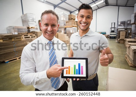 Warehouse team showing column graphic to the camera in a large warehouse - stock photo