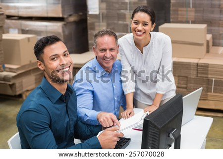 Warehouse team smiling at camera in a large warehouse - stock photo