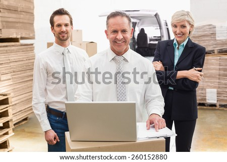 Warehouse team working together on laptop in a large warehouse - stock photo