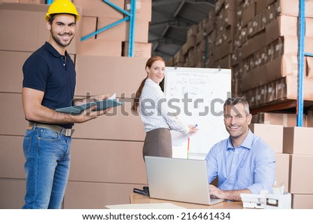 Warehouse team working together on shipment in a large warehouse - stock photo