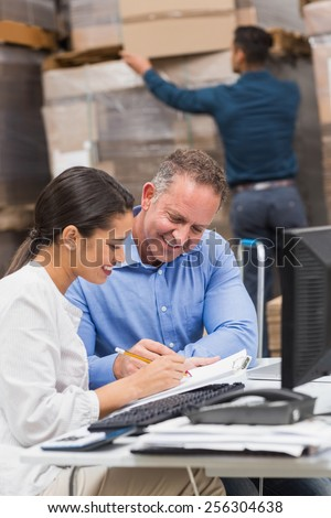 Warehouse team working together with clipboard in a large warehouse - stock photo