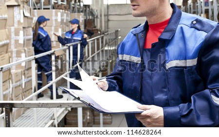 warehouse three workers- one man and two woman in a special blue uniform is recording and accounting of contents in cardboard boxes in stock No faces idea account statistics rediscount cargo arrival