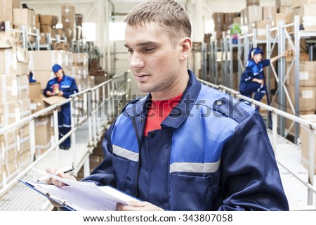 warehouse three workers - one man and two woman in a special blue uniform is recording and accounting of contents in cardboard boxes in stock.  idea account statistics discount cargo arrival - stock photo