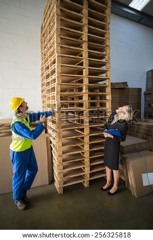 Warehouse worker and his manager looking stack of pallet in a large warehouse - stock photo