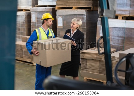 Warehouse worker and his manager working together in a large warehouse - stock photo