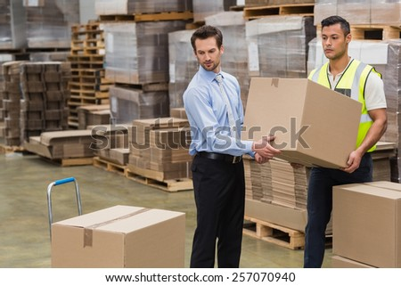 Warehouse worker and manager carrying a box together in a large warehouse - stock photo