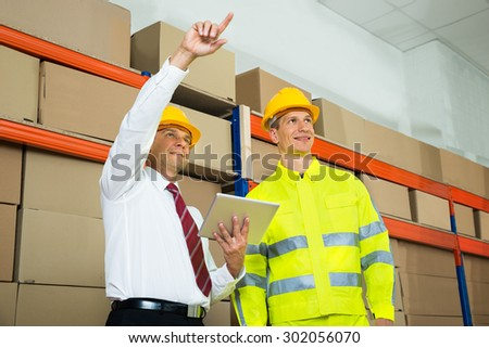 Warehouse Worker And Manager Checking The Inventory In A Large Warehouse - stock photo