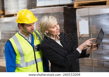 Warehouse worker and manager using tablet pc in a large warehouse - stock photo