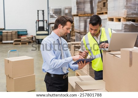 Warehouse worker and manager working together in a large warehouse - stock photo