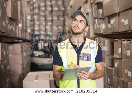 Warehouse worker checking his list in a large warehouse - stock photo