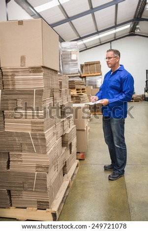 Warehouse worker checking his list on clipboard in a large warehouse - stock photo