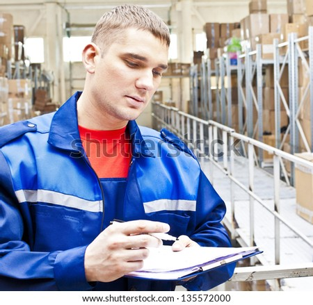 warehouse worker in a special uniform is recording and accounting of the contents in cardboard boxes in stock - stock photo