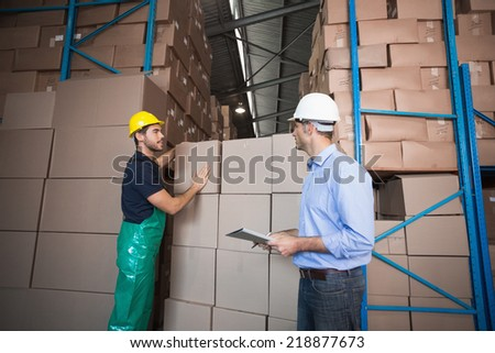 Warehouse worker loading up a pallet with manager in a large warehouse