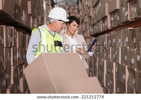 Warehouse worker moving boxes on trolley talking to manager in a large warehouse - stock photo