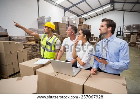 Warehouse worker pointing something to his colleagues in a large warehouse - stock photo