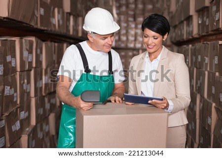 Warehouse worker scanning box with manager holding tablet pc in a large warehouse - stock photo