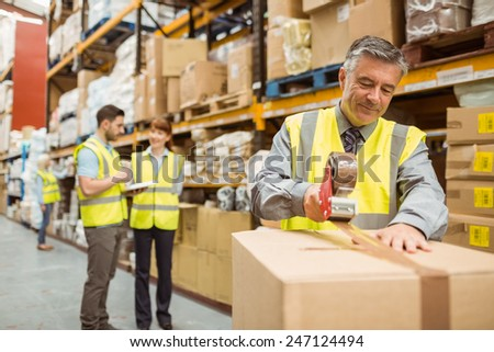 Warehouse worker sealing cardboard boxes for shipping in a large warehouse - stock photo