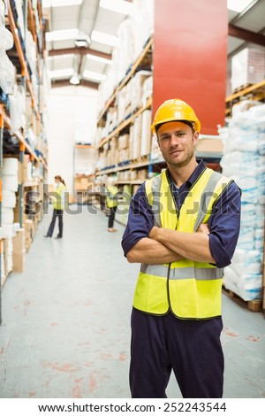 Female warehouse worker stock images royalty free images warehouse worker smiling at camera with arms crossed in a large warehouse sciox Choice Image
