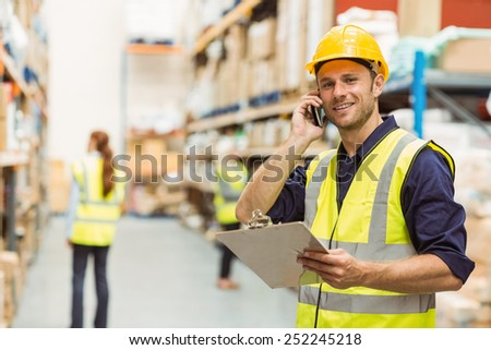 Warehouse worker talking on the phone holding clipboard in a large warehouse - stock photo