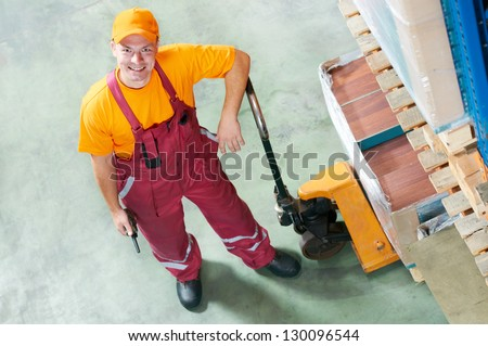 warehouse worker with fork pallet truck stacker - stock photo