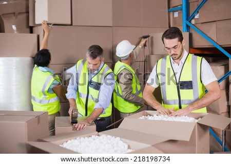 Warehouse workers in yellow vests preparing a shipment in a large warehouse - stock photo