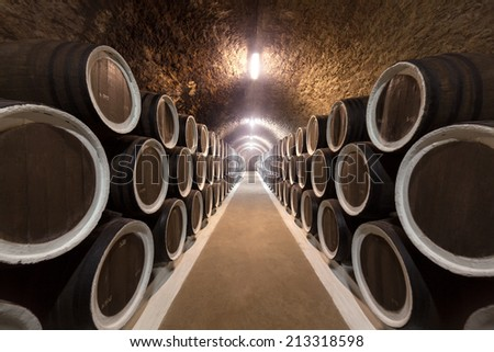 Warehoused barrels in the wine cellar - stock photo