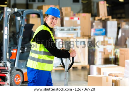 Warehouseman in protective vest pulls a mover with packages and boxes at warehouse of freight forwarding company- a forklift is in Background - stock photo