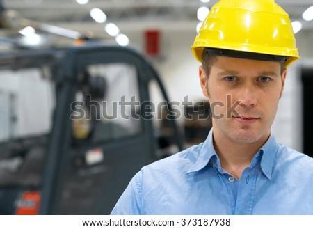 Warehouseman in yellow hard hat at warehouse. - stock photo