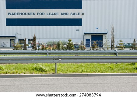 Warehouses for lease and sale sign on a warehouse building in the city. - stock photo