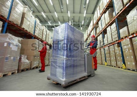 warehousing - management of the flow of resources - two workers in uniforms and safety helmets working in storehouse - stock photo