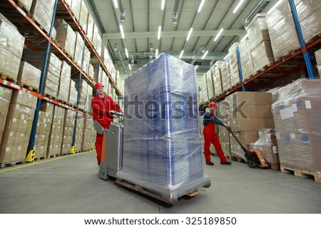 Warehousing - Two workers in uniforms working in storehouse - stock photo